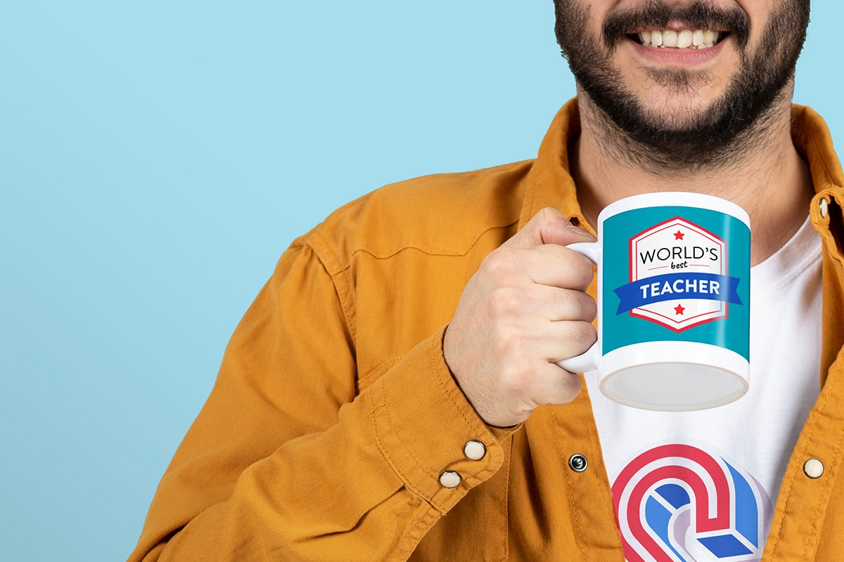 A man in a mustard-coloured shirt, against a blue background, holding a customised mug with 'world's best teacher' on.
