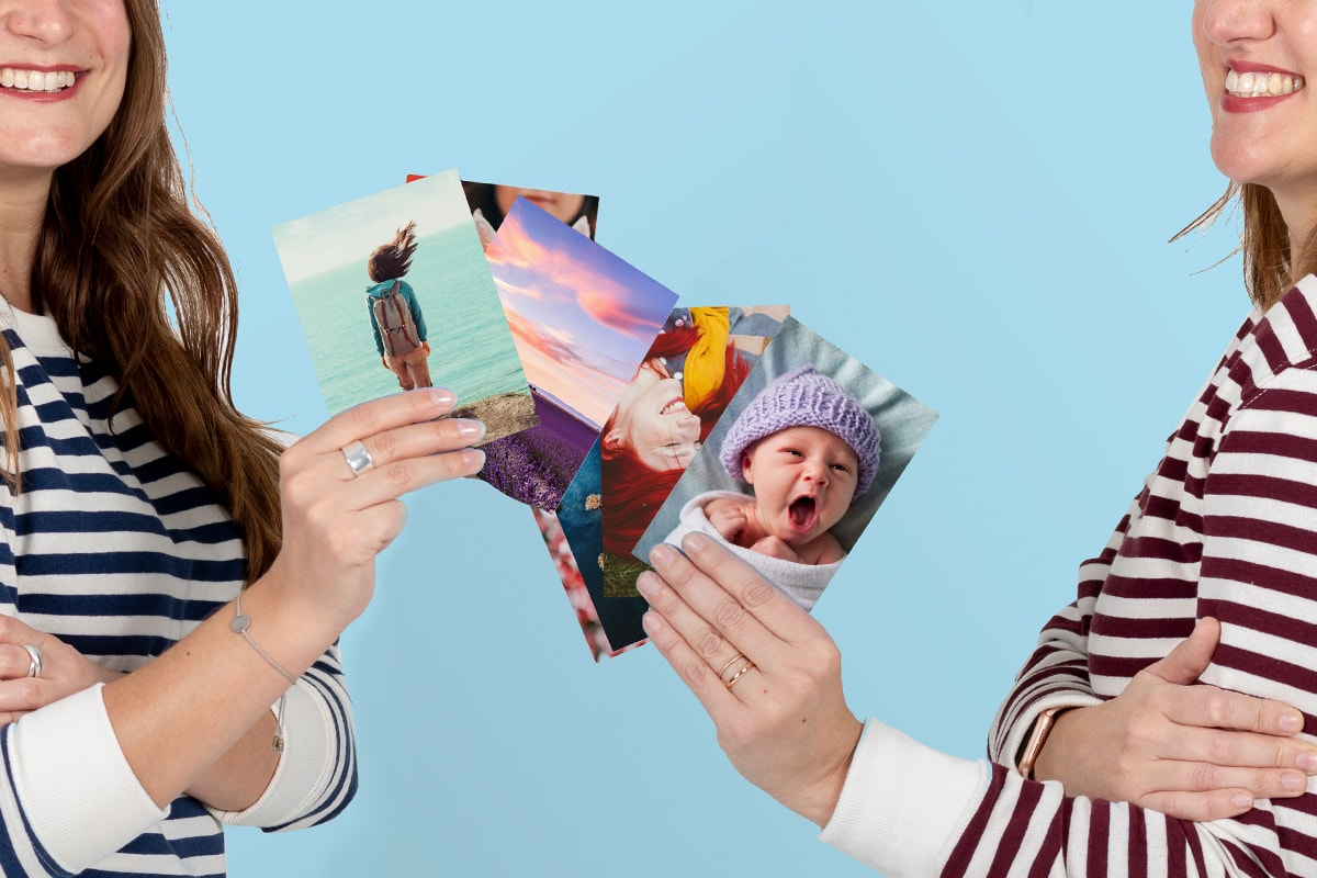 Two women wearing stripey tops, holding photo prints next to each other.