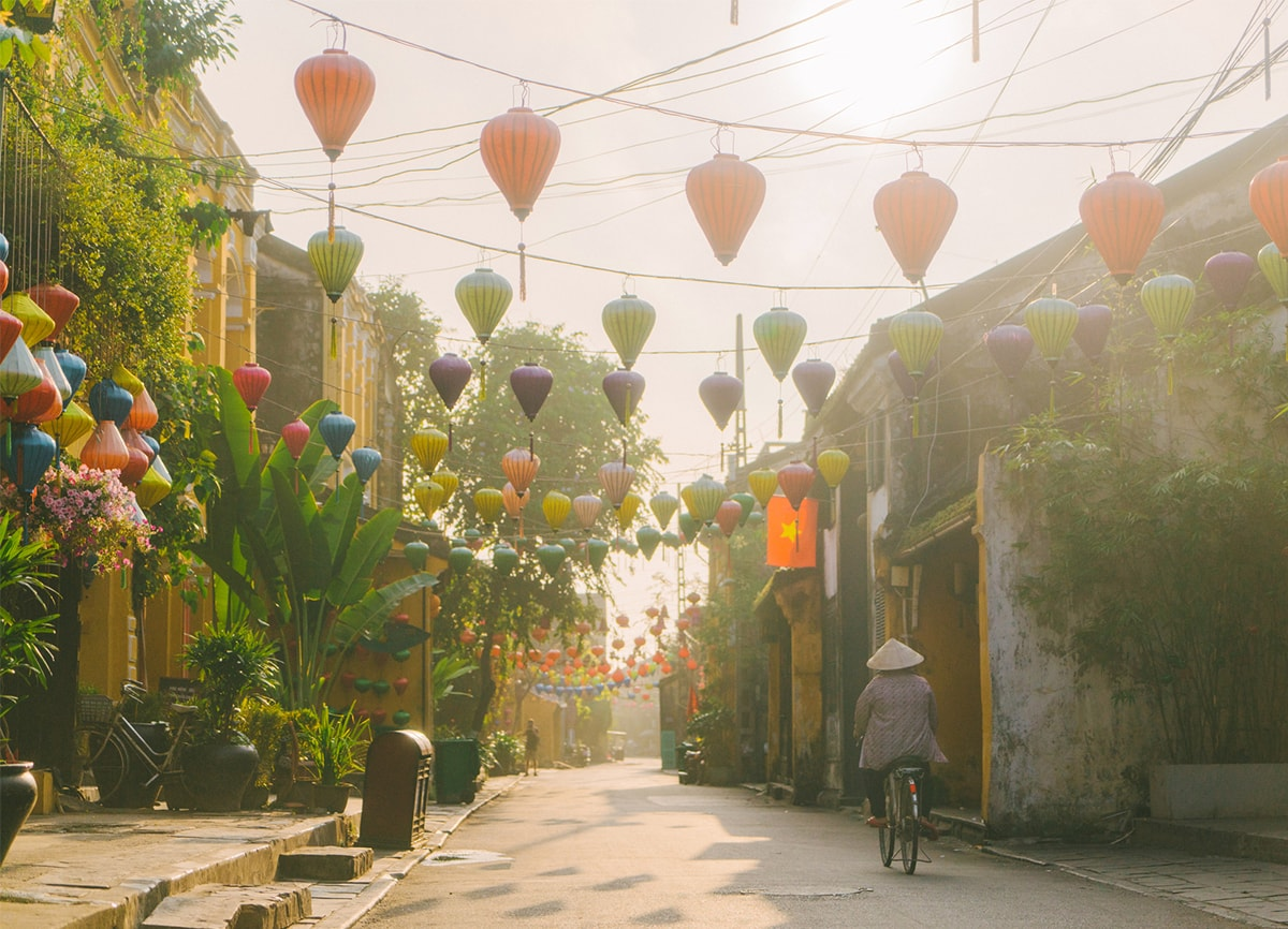 A woman cycling in a street on a hazy sunny day. The street is covered in brightly coloured paper lanterns hanging overhead.