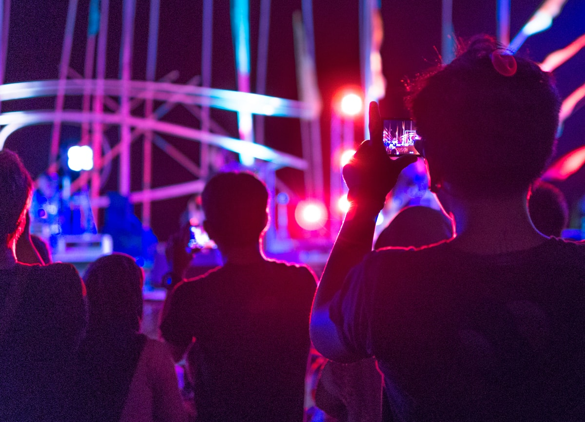 An image of people in a crowd at a concert. The lighting is low, and everything in the background, including the stage, is out of focus.