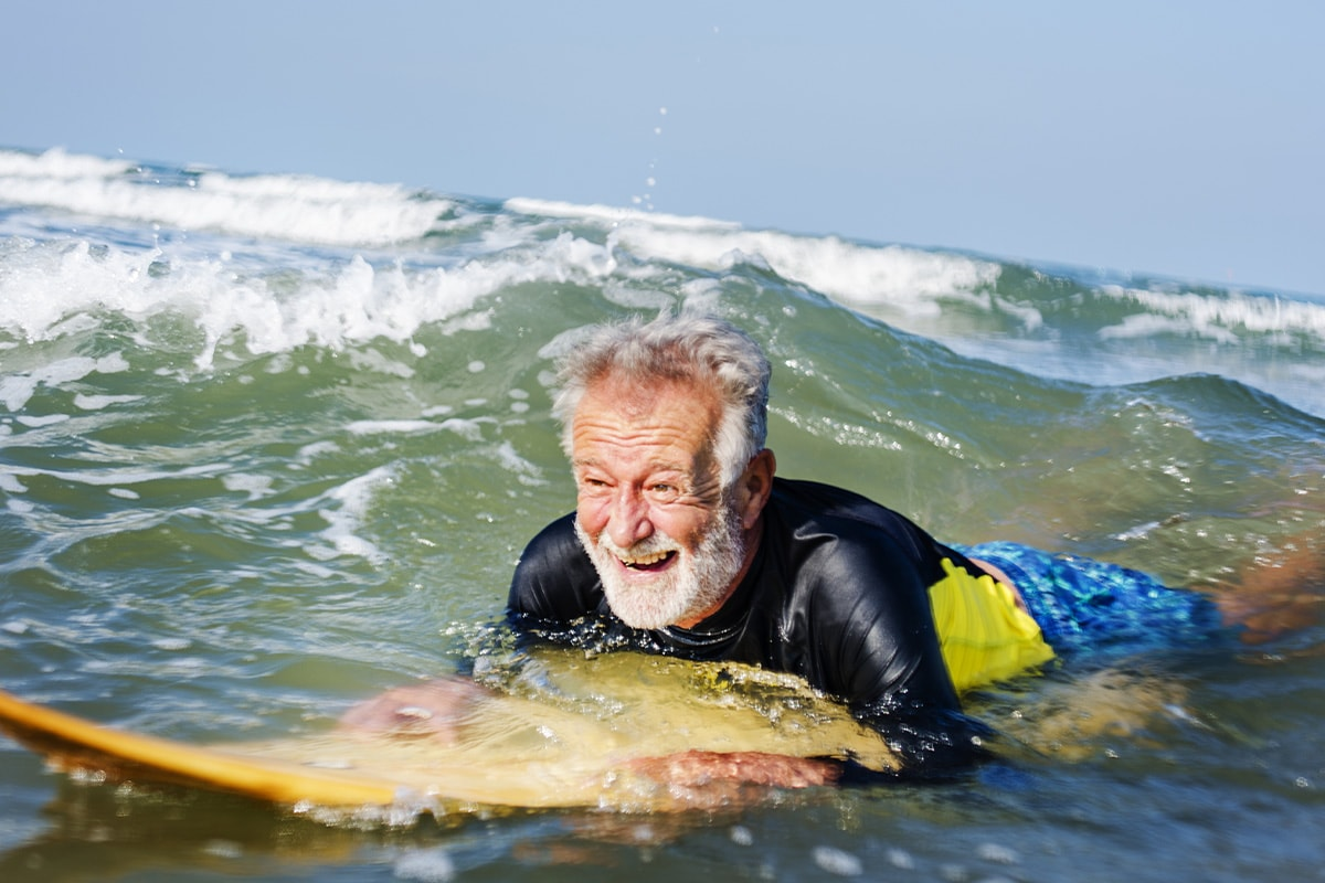 An older man smiling on a surfboard in the sea.