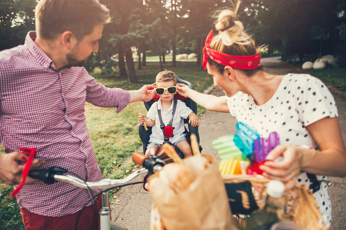 A young couple in a park with bikes, placing sunglasses on their young son in the bike seat.