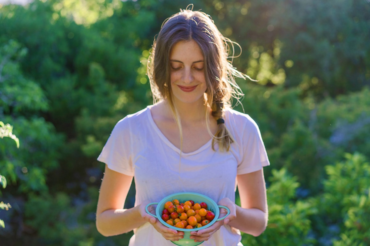 A young woman in the forest with a bowl of freshly picked fruit