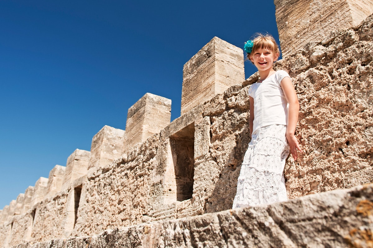 A young girl on the battlements of an old castle underneath a bright blue sky.