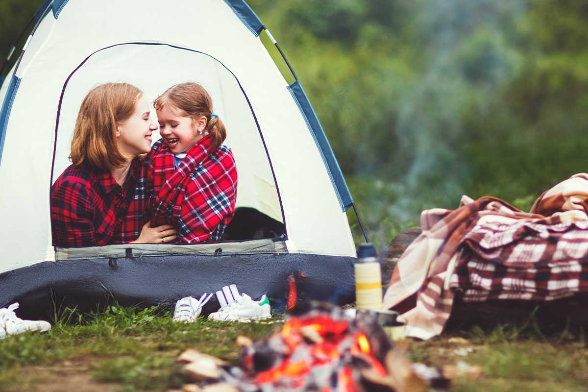 A mother and daughter smiling in a tent in front of a campfire