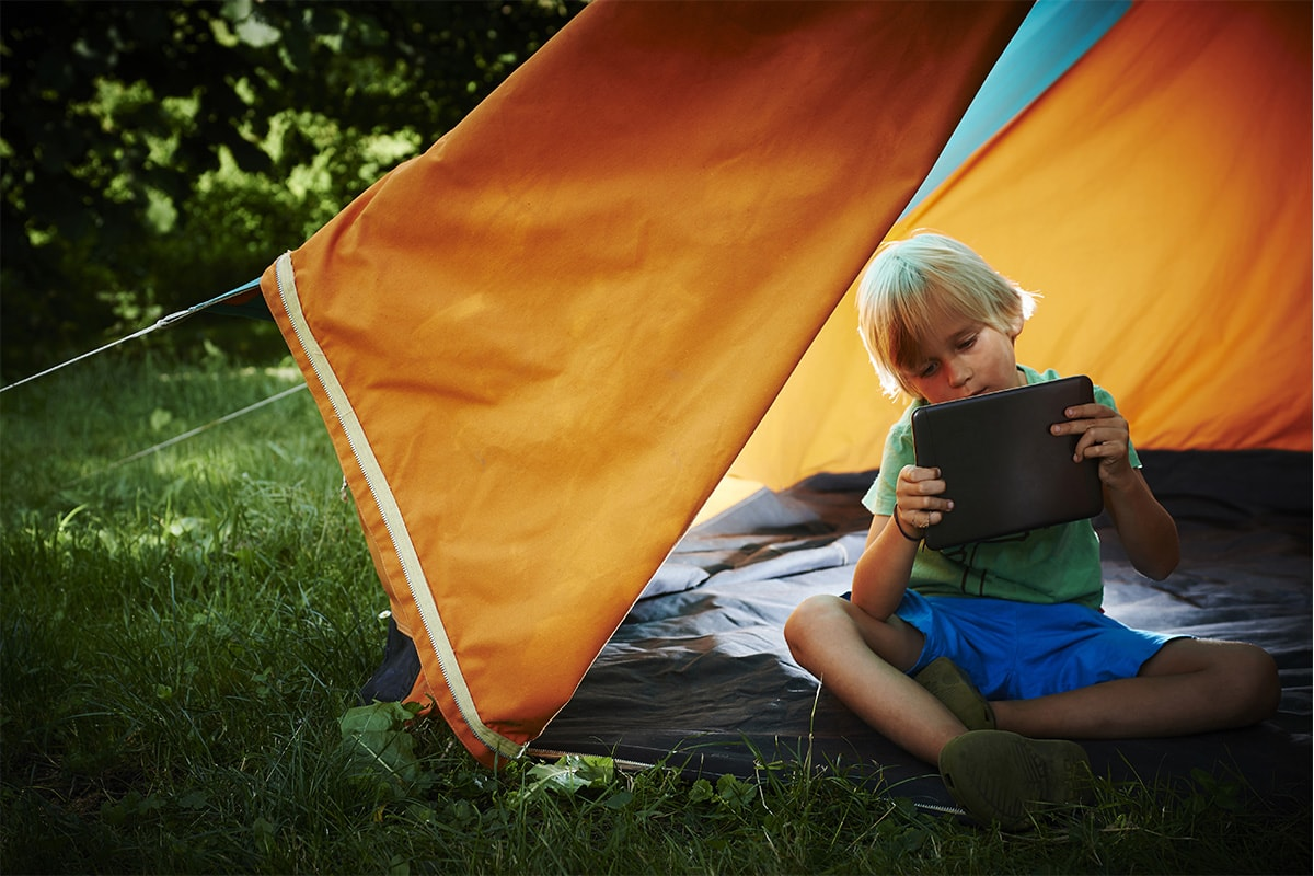 A young boy holding a tablet in an orange tent in the woods.