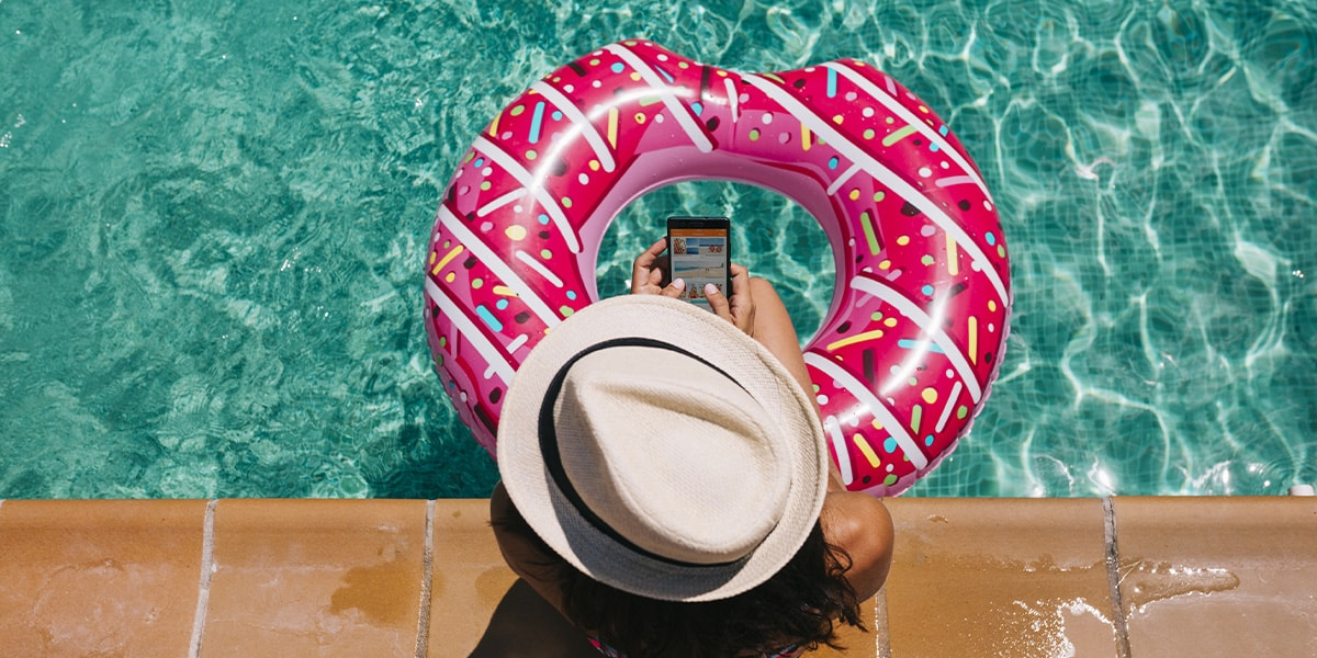 A woman sat by the pool with her legs in a pink rubber ring, holding a mobile phone.