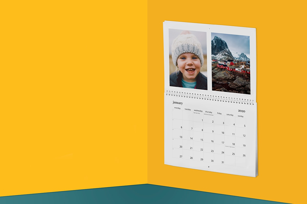 A photo calendar on a yellow wall showing a young child in a wooly hat
