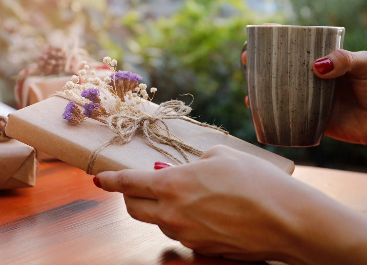 A hand holding a book wrapped in brown gift wrap, tied up with string and small purple and white flowers attached to it.