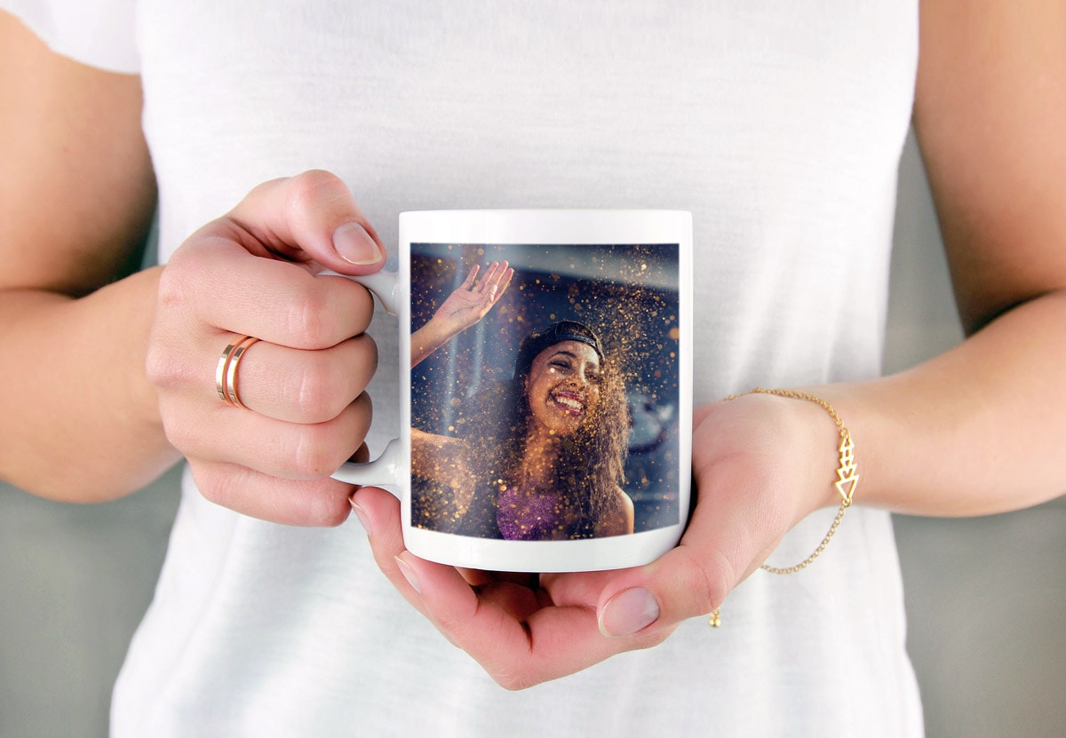 A close-up of a woman holding a photo mug with a picture of a woman at a festival on the side.