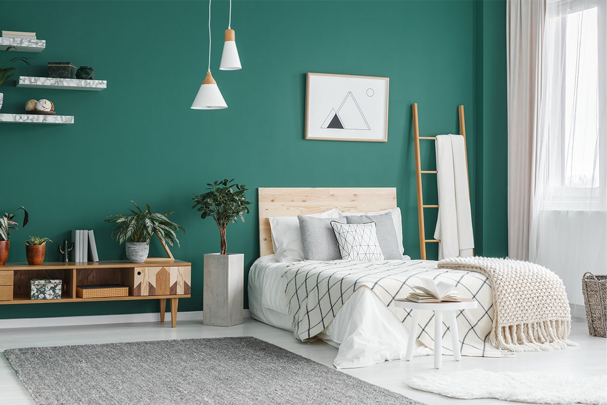 A bedroom with an emerald green feature wall, with a bed covered with white, grey, and tan bedding, marble shelves on the wall and a wooden side table.