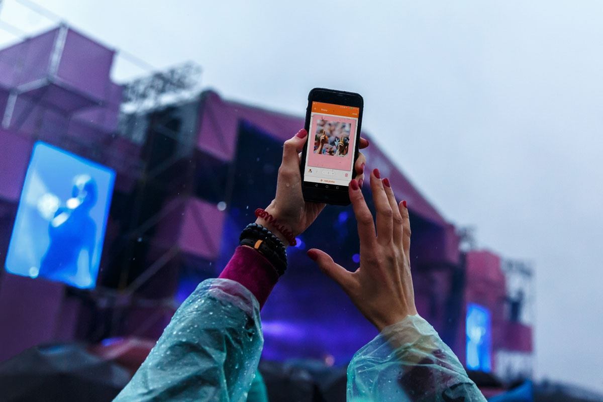 A photo of a woman holding up her phone in front of a stage at a festival, with a coloured retro print on the screen.