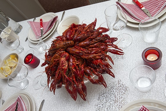 Tray full of boiled red crayfish placed in the middle of the table.