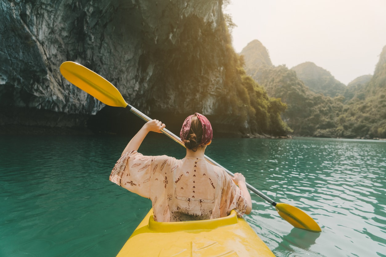 A girl with her back facing the camera, kayaking on the sea. There are mountains and cliffs in the background that are slightly blurred.