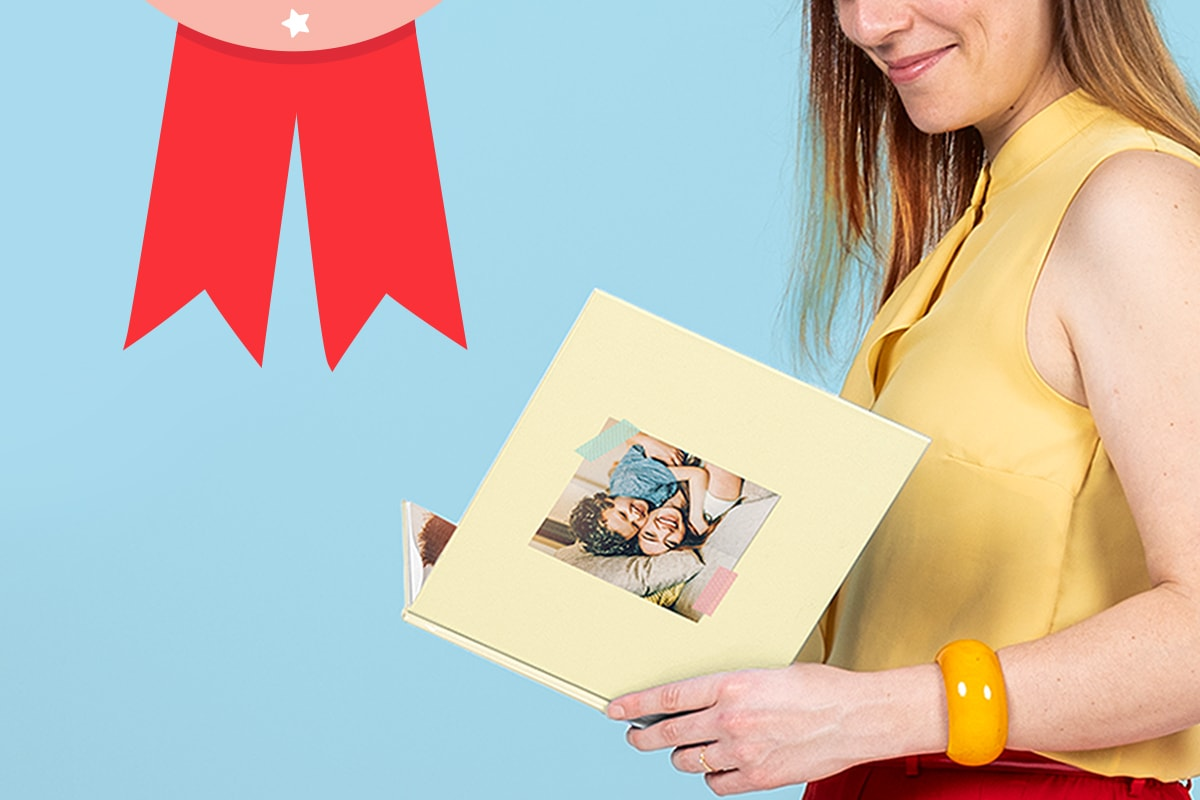 A photo of a woman dressed in yellow and red, against a pale blue background, reading a yellow customised photo book.
