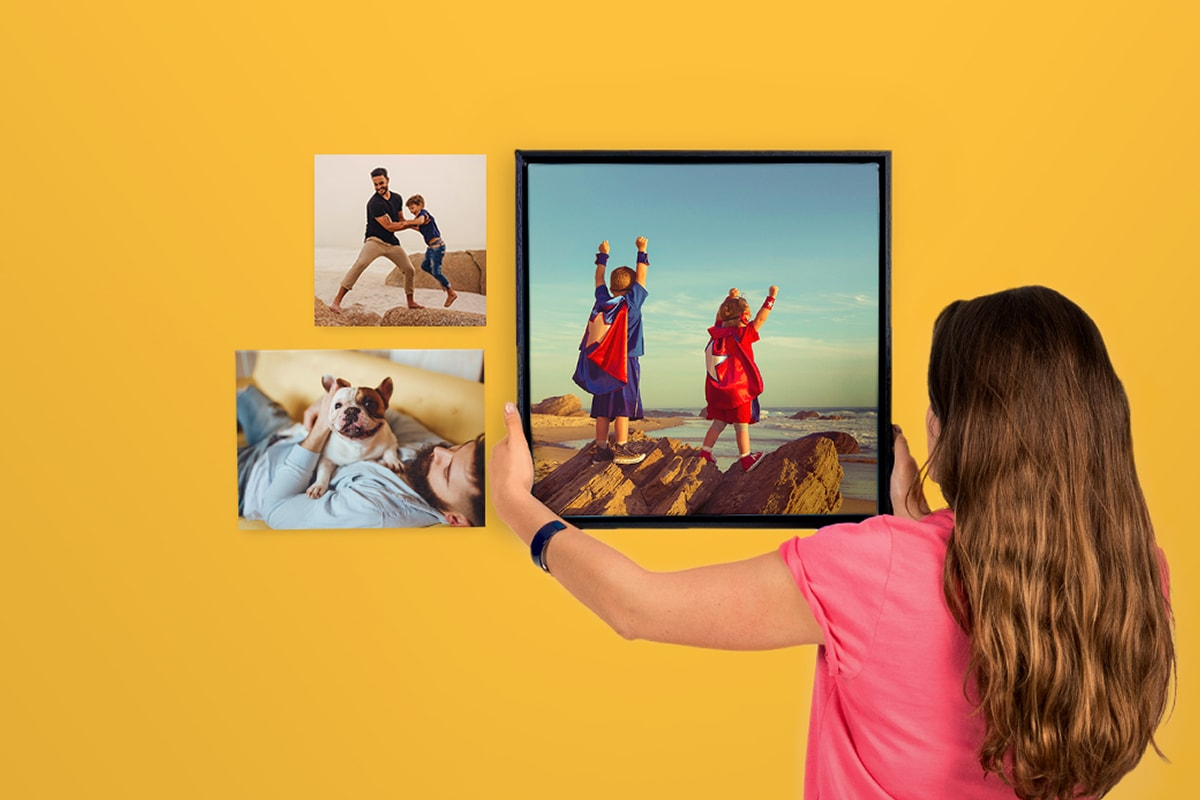 A photo of a woman in a pink t-shirt, hanging a canvas wall art of two kids in superhero costumes, against a bright yellow wall.