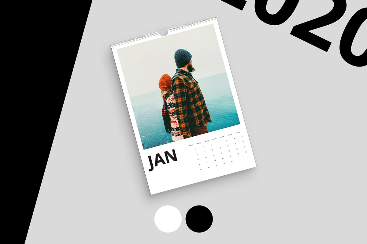 Un calendrier avec une photo d'un couple en tenue hivernale regardant, dos à dos, la mer à l'horizon